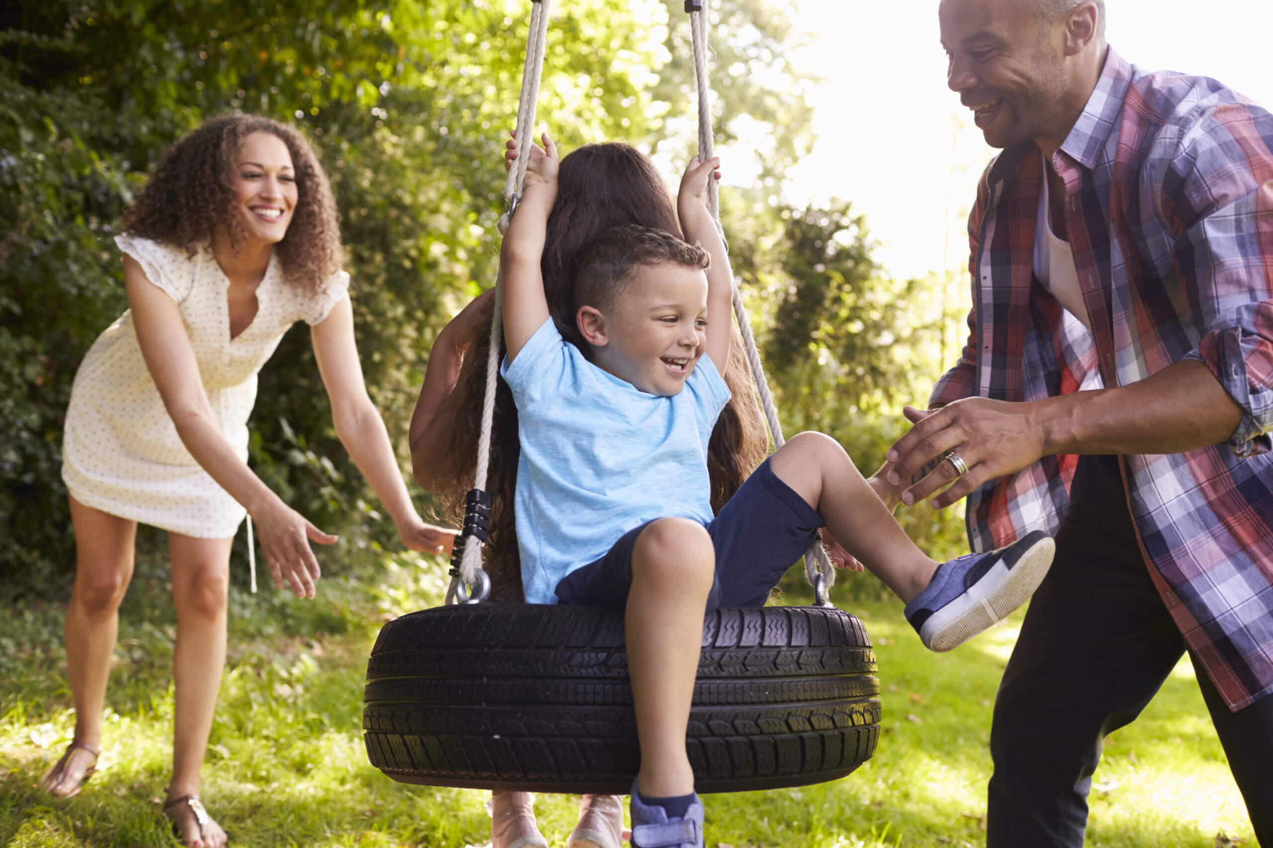 Happy family playing outside on a tire swing